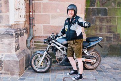Mann in Lederhosen mit Motorrad