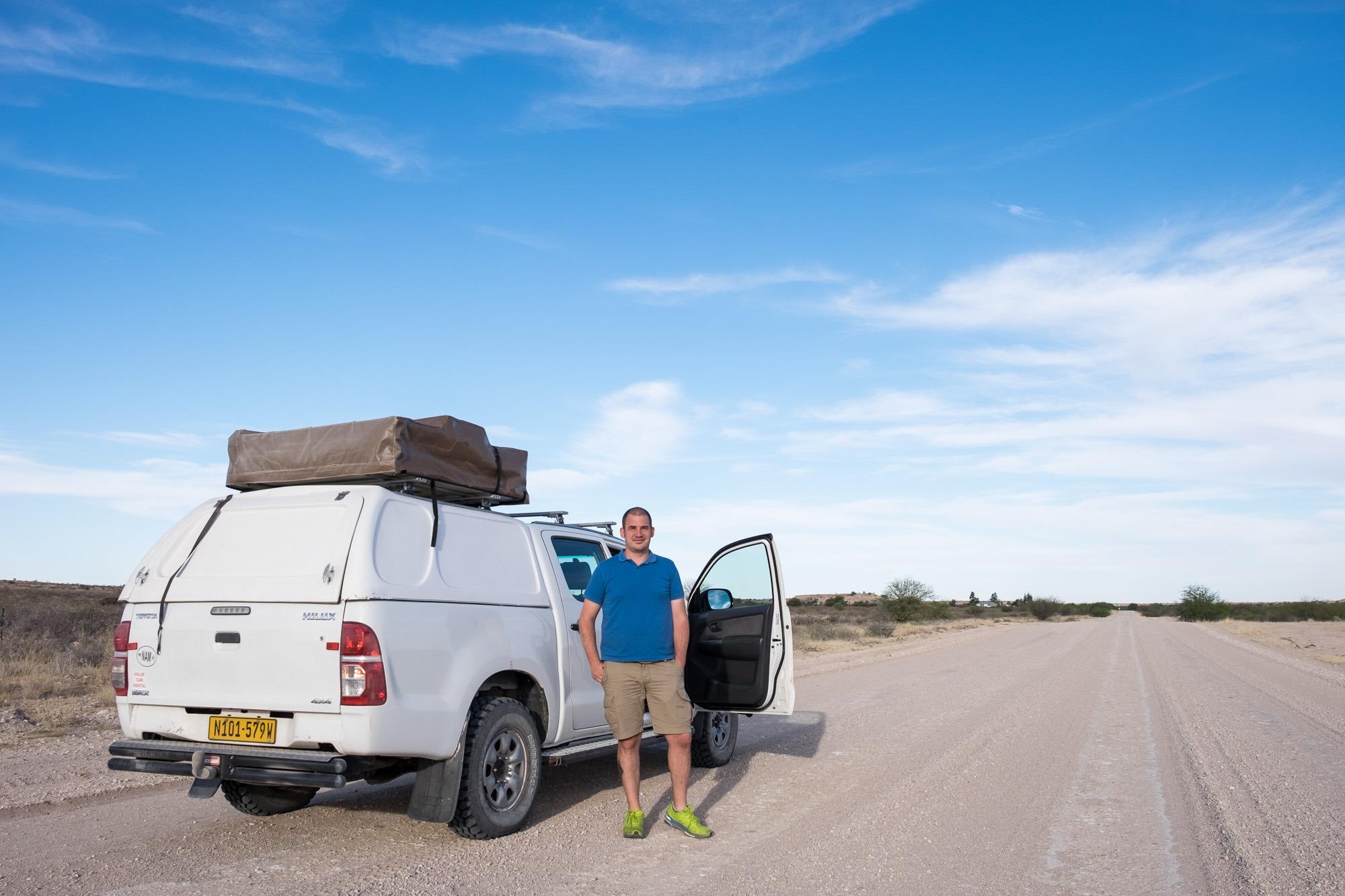 Toyata Hillux mit Mann auf Schotterpiste in Namibia