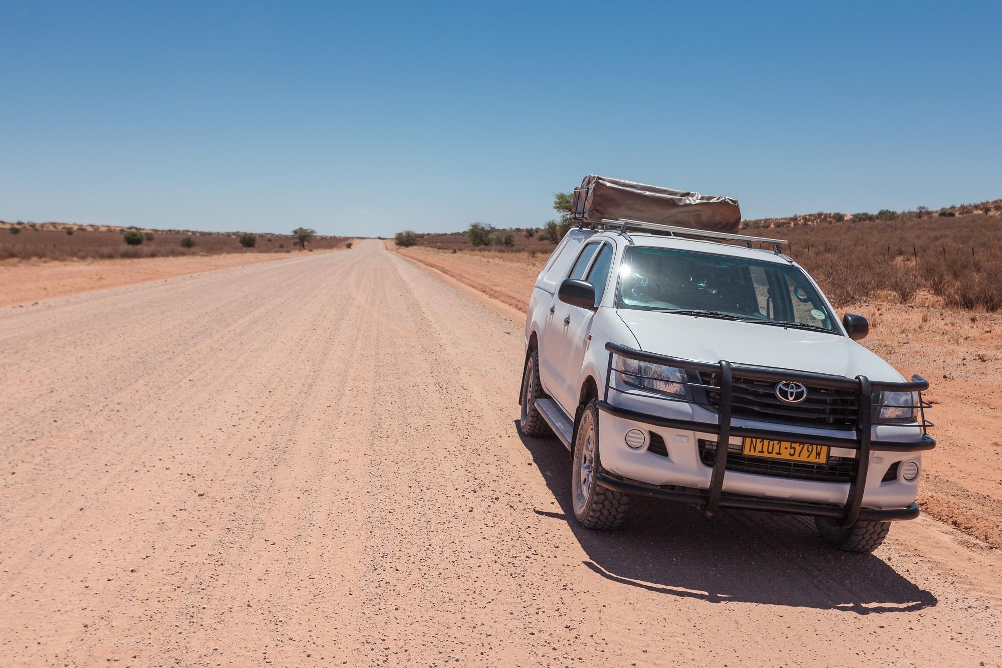 Toyata Hillux auf langer, gerade Strasse auf einer Staubpiste in Namibia