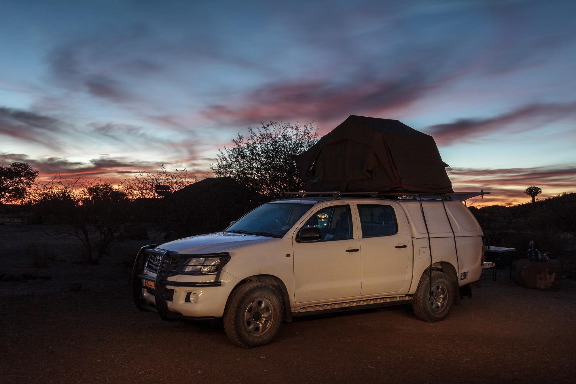 Toyata Hillux mit Dachzelt im Sonnenuntergang in Namibia