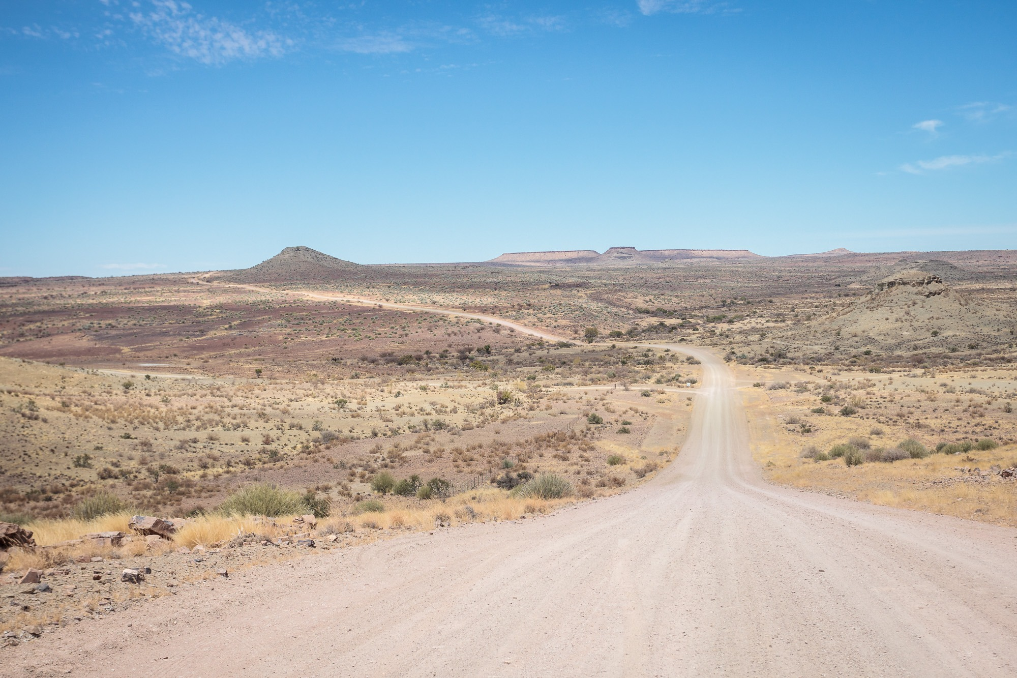 Gerade Staubpiste in der Wüste mit blauem Himmel in Namibia