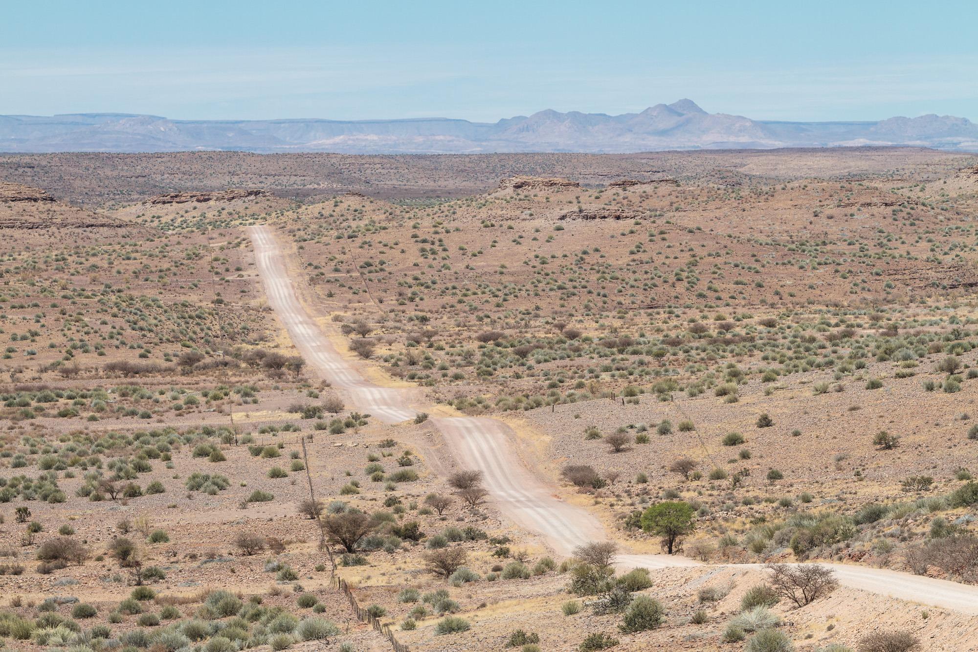 Gerade Staubpiste in einer Wüste in Namibia