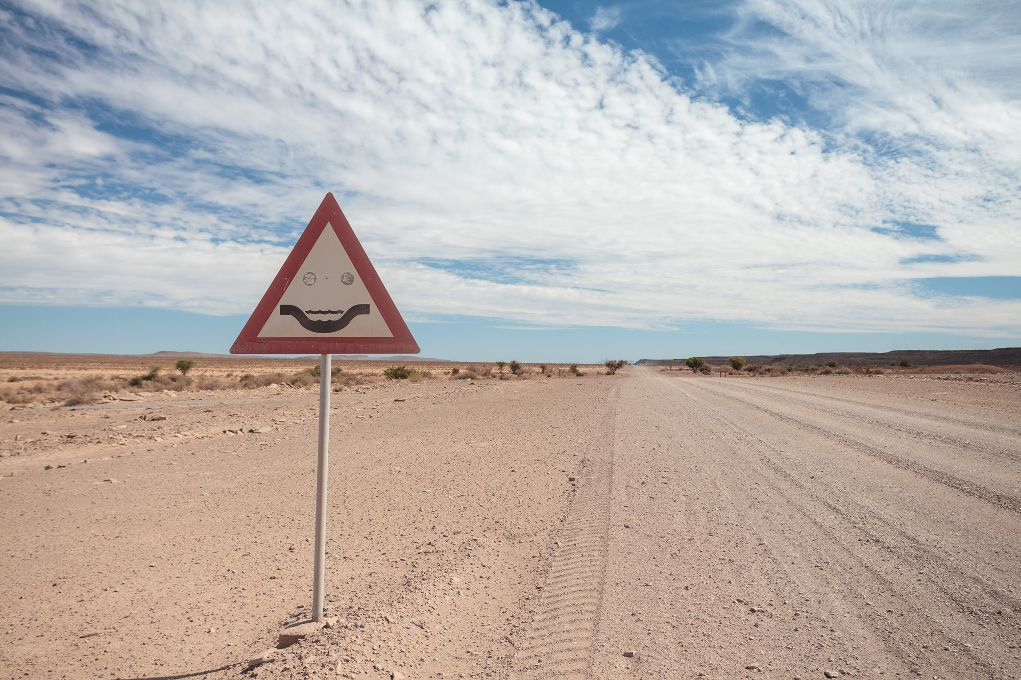 Strassenschild Trockenfluss in Namibia als Smiley