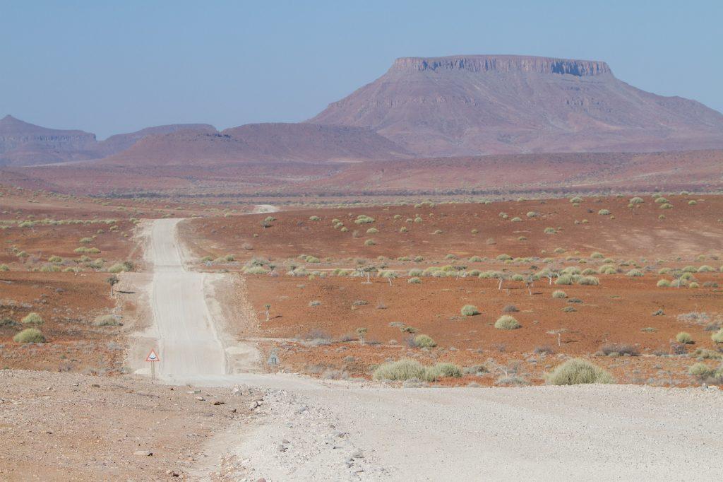 Hügelige Schotterpiste inmitten von rotem Sand in der Damarawüste