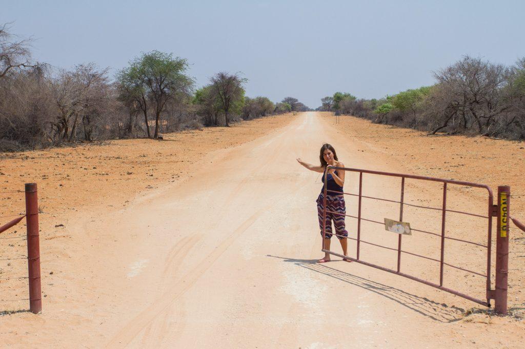 Frau öffnet Gatter auf einer roten Schotterpiste in Namibia