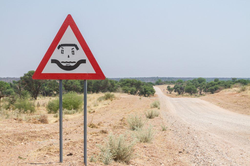 Trockenflussbett Warnschild, Straßenschild mit Smiley in Namibia